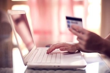 Woman holds credit card and does online payment with laptop. Online shopping concept