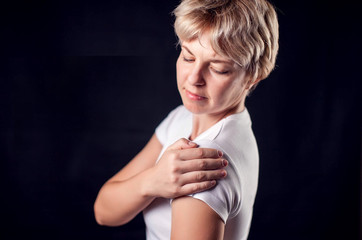 Woman feels strong pain in shoulder. People, healthcare and medicine concept