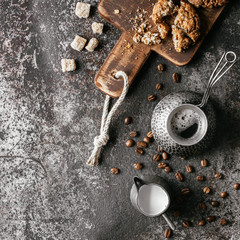 Wall Mural - Coffee beans with coffee and cookie on dark textured background.