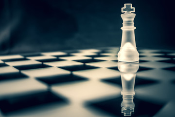 White frosted glass King chess piece on chess board