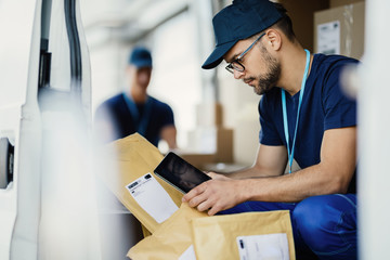 Delivery man scanning package bar code with a touchpad in a van.