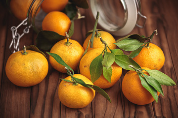 tangerines and glass jar on wooden surface