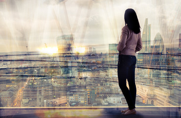 Young woman looking over the City of London at sunset. Beautiful city background in gentle light. Future, freedom, business success and new opportunity concept