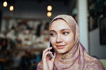 muslim woman in a scarf speaks on the phone with a gentle smile