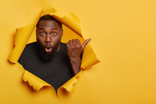Gosh, look here! Shocked dark skinned unshaven man points thumb away, feels impressed and stunned, wears black casual t shirt, stands in torn paper hole of yellow background, has eyes popped out