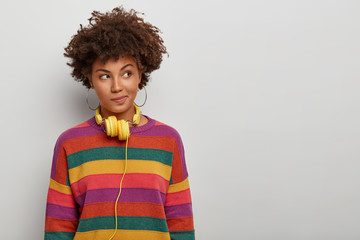 Photo of thoughtful curly haired woman looks aside with pensive expression, wears headphones and striped jumper, has plan in mind, poses over white background, blank space for your advertising content