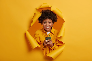 Happy curly haired student laughs at funny joke in social networks, smiles toothily, plays game online on modern cellphone, dressed in stylish outfit, stands in ripped hole background, yellow color Wall mural