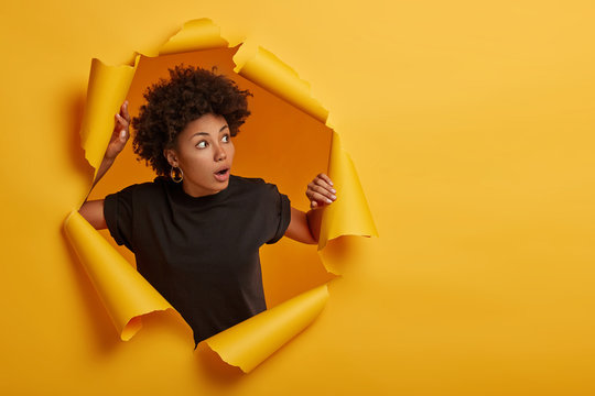 Photo of surprised Afro woman in black t shirt gasps from amazement, looks with scared face expression aside, dressed in black t shirt, unexpected to see something horrible, poses in torn paper wall