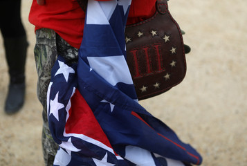 """An attendee carries a Confederate flag, a Trump flag and a bag with the III% sign as militia members and pro-gun rights activists participate in the """"Declaration of Restoration"""" rally listen to speakers in Washington, D.C."""