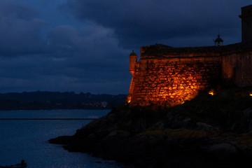 Faro, garita de vigilancia y parte de la muralla del Castillo de San Antón de La Coruña con su iluminación nocturna