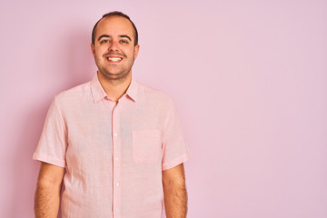 Young man wearing elegant shirt standing over isolated pink background with a happy and cool smile...