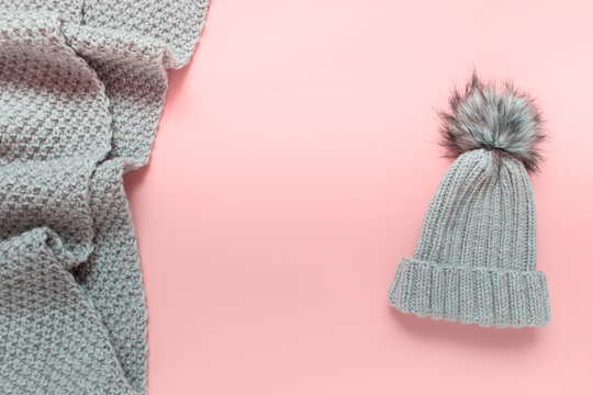 Warm winter wardrobe handmade hat beanie with pompom and knitted large scarf on pink background. Photo with copy blank space in the center of image.