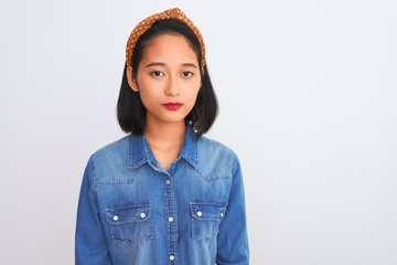Young beautiful chinese woman wearing denim shirt standing over isolated white background with serious expression on face. Simple and natural looking at the camera. Wall mural