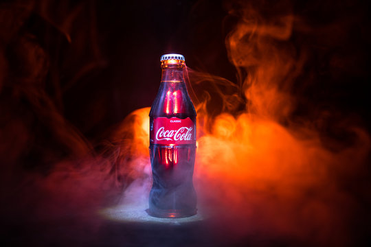 Baku, Azerbaijan 13th January 2018, Coca-Cola Classic in a glass bottle on dark toned foggy Background. Coca Cola is the most popular carbonated soft drink beverages sold around the world