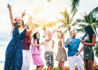 Group of happy people of mixed race friends celebrate Christmas and New Year at a tropical resort in Santa hats with glasses of champagne in their hands.