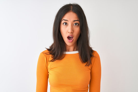 Young beautiful chinese woman wearing orange t-shirt standing over isolated white background afraid and shocked with surprise expression, fear and excited face.
