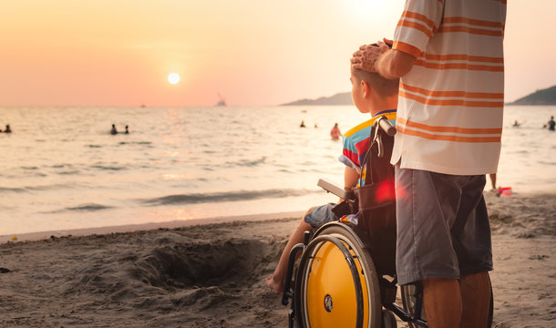 Father and Asian special child on wheelchair is happily on the beach, Dad and son spend holiday to travel and learning about nature around the sea,Life in the education age,Happy disabled kid concept.