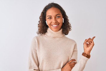 Brazilian woman listening to music using wireless earphones over isolated white background very happy pointing with hand and finger to the side