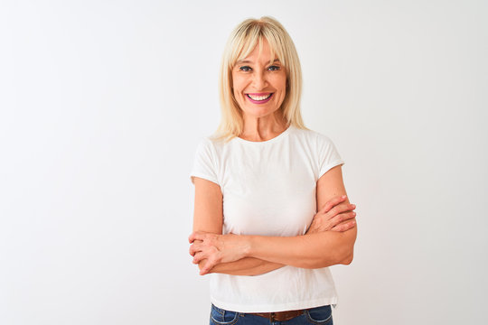 Middle age woman wearing casual t-shirt standing over isolated white background happy face smiling with crossed arms looking at the camera. Positive person.