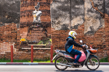 Ayutthaya, Thailand - September, 29, 2019 : Motion blur picture of unidentified name people are riding a motorcycle on the road in front of the abandoned temple at Ayutthaya, Thailand