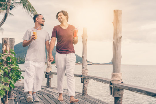 Happy handsome young men, gay family in a tropical resort with fruit necks, LGBT values, equal rights for everyone. Vacations and Travel