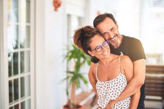 Middle age beautiful couple standing on terrace hugging and smiling