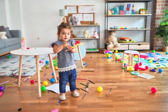 Beautiful toddler holding yellow pen standing around lots of toys smiling at kindergarten