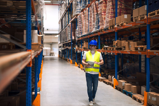 Warehouse worker looking at shelves with packages and walking through large warehouse storage distribution area.
