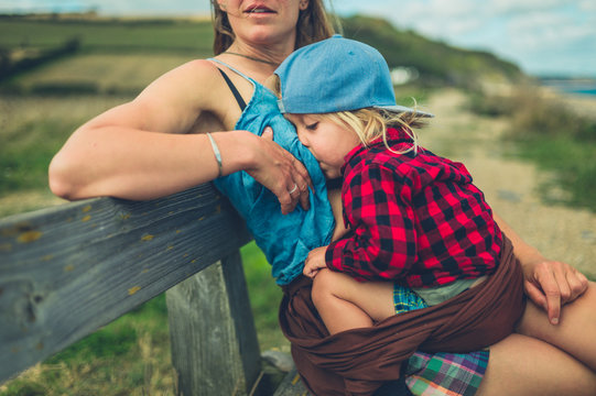 Young mother breastfeeding her toddler on bench by the sea