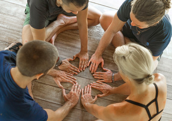 group of young hipster American friends enjoying Asian yoga retreat together sitting on lotus position joining hands on wooden hut floor meditating outdoors  in harmony