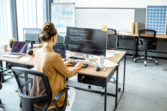Young woman working as a programmer, writing programming code on the computer at the coworking space