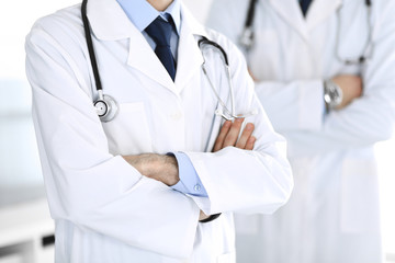 Doctor man standing straight and crossed arms with colleague at background, close-up. Group of doctors. Perfect medical service in clinic. Medicine and healthcare concepts. Toned picture