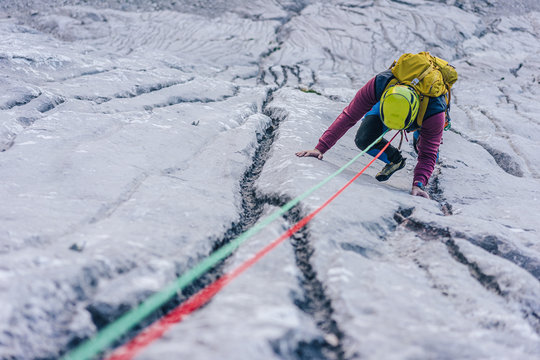 A climber climbing on a big rock wall. A mountaineer ascending a climbing route. Limestone climbing in the alps. Adventure extreme sport activity. Multi pitch climbing in huge alpine wall.