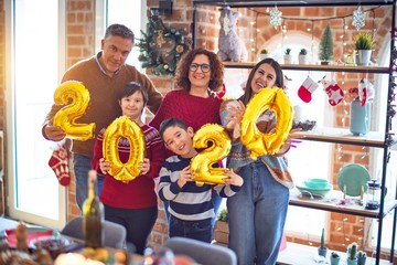 Beautiful family smiling happy and confident. Standing and posing holding 2020 balloons celebrating new year at home