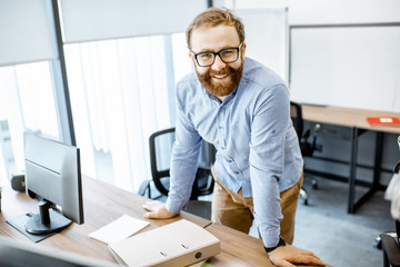 Portrait of a handsome bearded office worker dressed casually during a work in the office Wall mural