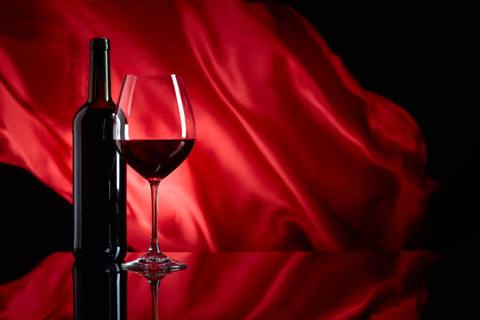 Wineglass and bottle of red wine on a black reflective background.
