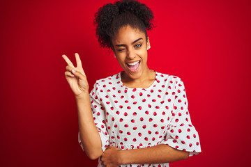 African american woman wearing fashion white dress standing over isolated red background smiling with happy face winking at the camera doing victory sign. Number two.