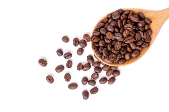 Closeup roasted coffee beans in wooden spoon isolated on white background. Top view. Flat lay.
