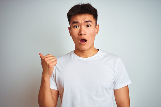 Young asian chinese man wearing t-shirt standing over isolated white background Surprised pointing with hand finger to the side, open mouth amazed expression.