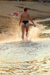 A young girl runs along the shore of the beach