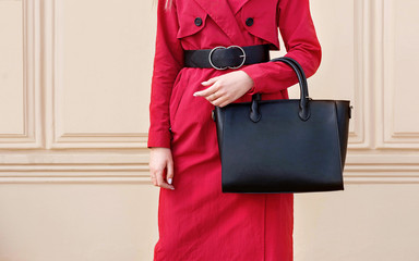 Wall Mural - Autumn trendy woman in red coat with black handbag. Stylish outfit