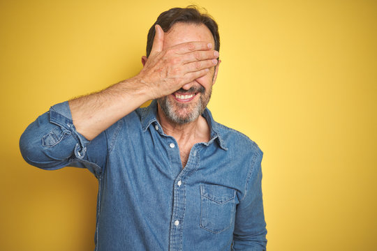 Handsome middle age senior man with grey hair over isolated yellow background smiling and laughing with hand on face covering eyes for surprise. Blind concept.