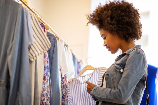 Side of beautiful young black woman with afro  shopping for clothes in store