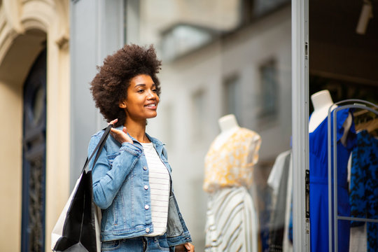 young african american woman window shopping for clothes by store