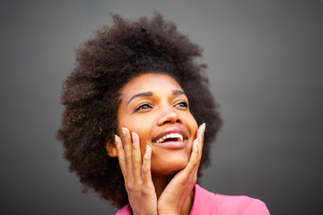 Close up of beauty young african american woman smiling with hands on face against gray wall
