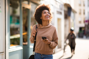 happy young black woman with phone walking in city