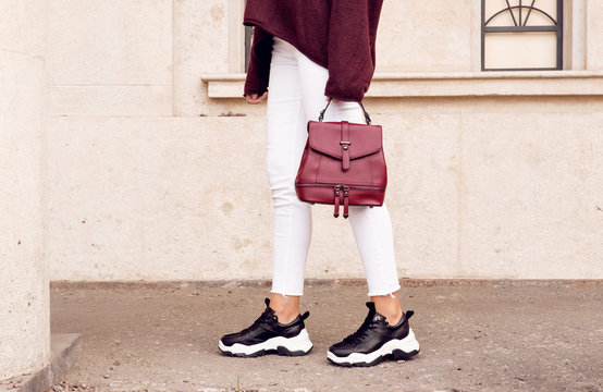 woman in fashion sneakers with red bag near beige wall.