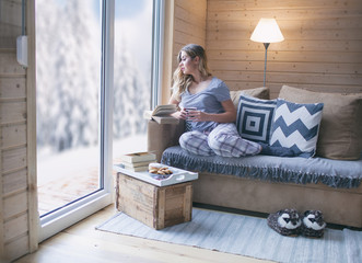 Young beautiful blonde woman with book sitting home in living room by the window. Winter snow landscape view.