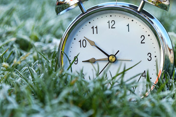 The alarm clock is in the grass covered with frost