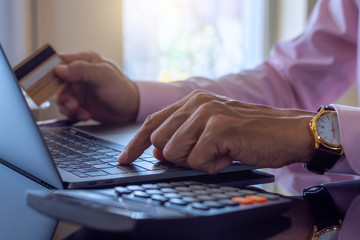 Business man makes online payment and internet banking by using laptop computer notebook and credit or debit card with calculator on the desk at home . Online banking, e business, e-commerce concept.